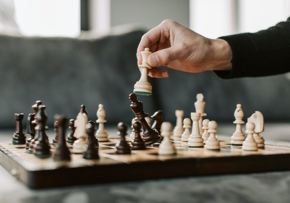 Hand moving pieces over chess board