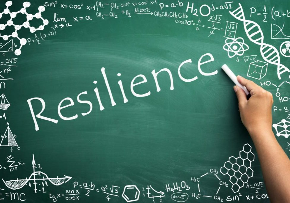 """The word """"resilience"""" on a chalkboard surrounded by scientific symbols and graphics"""
