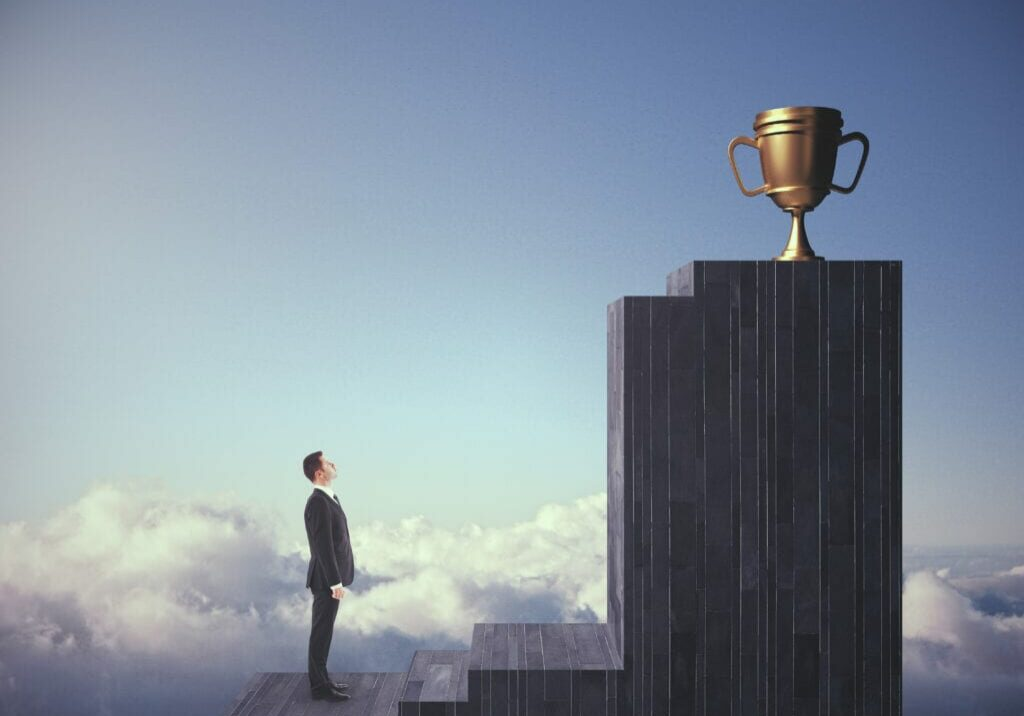 Man looking at a gold trophy on a pedestal
